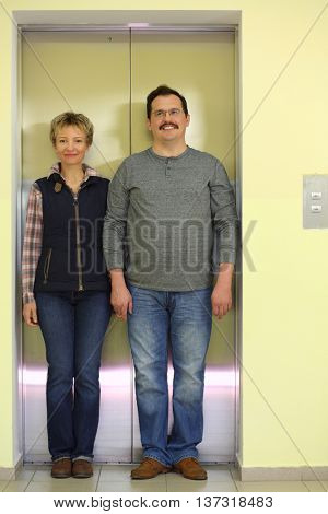 Portrait of husband and wife in front of a closed elevator