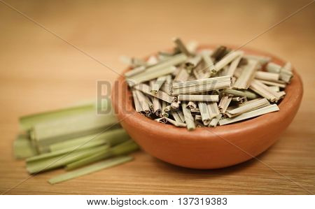 Lemongrass in a bowl on wooden surface