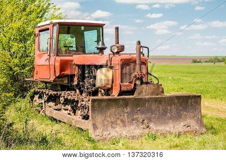 Red old rusty tractor in a field.