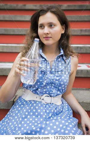 Young woman with blue polka dot dress sitting with carbonated water in a clear bottle in hand