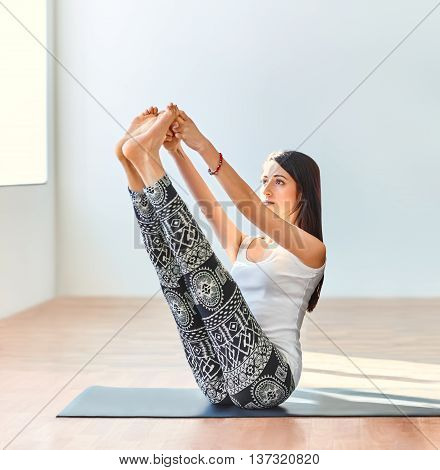 Young woman doing yoga asana both big toes pose. Ubhaya Padangusthasana