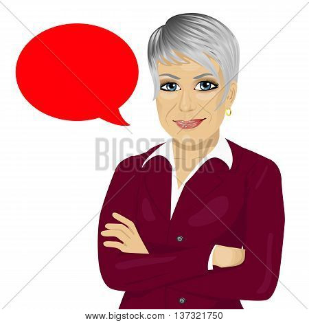 attractive senior businesswoman with arms folded standing near red blank speech bubble isolated on white background