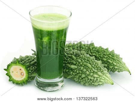 Herbal juice of green momodica in a glass with fresh vegetables