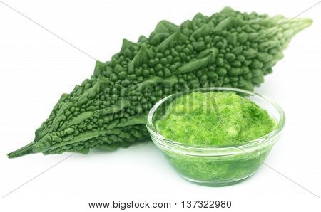 Green momodica with paste in a glass bowl over white background