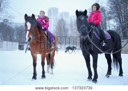 Two girls sitting on horseback at the equestrian site near the residential complex