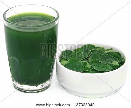 Moringa leaves with extract in a glass over white background