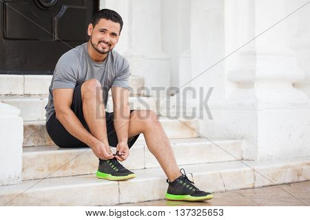 Latin Runner Tying His Shoes Outdoors