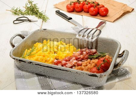 british breakfast with scrambled eggs in a roasting tin smoked bacon cubes baked beans fresh tomatoes rosemary