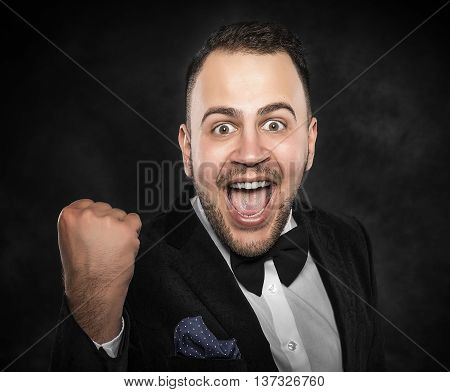 Young man cellebrate on a dark background.