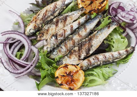 Grilled sardine fish with lettuce, lemon and onion