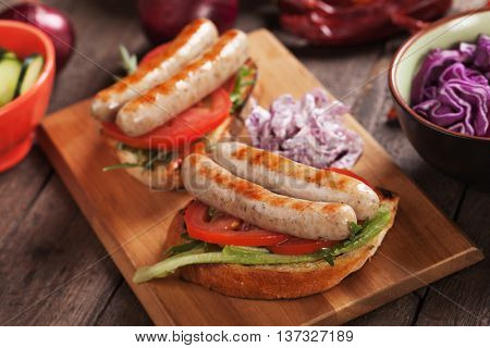 Grilled sausage sandwich with toasted bread, tomato and coleslaw salad