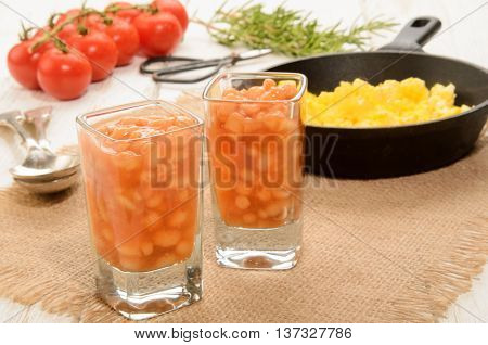 baked beans in a shot glass scrambled eggs in a cast iron pan fresh tomatoes rosemary and herbal scissor
