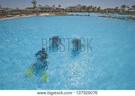 Three scuba divers training underwater in luxury tropical hotel resort swimming pool