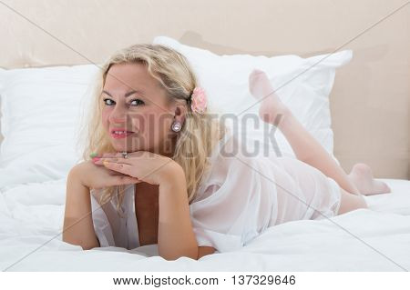 Sexy woman in white stockings and lingerie. Portrait of blonde girl posing on bed.