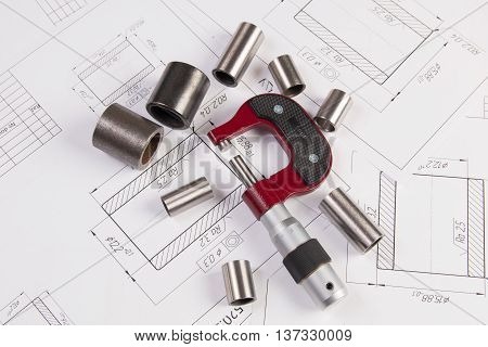 Metal cylinders, micrometer and calipers on printed engineering drawings. Mechanics and Engineering Technology. Engineering drawings of steel parts