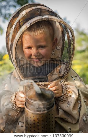 Young farm beekeeper boy using a smoker on bee yard