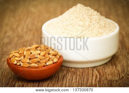 Wheat and reddish flour in a bowl on wooden surface