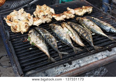 Plenty of chicken tabaka and fish grilled at barbecue. Mackerel bbq outdoors at picnic, party. Street food, roasted meat and seafood grill takeaway at grate