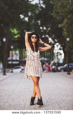 Beautiful young woman posing in a street at sunset. Full body shot of model wearing summer dress