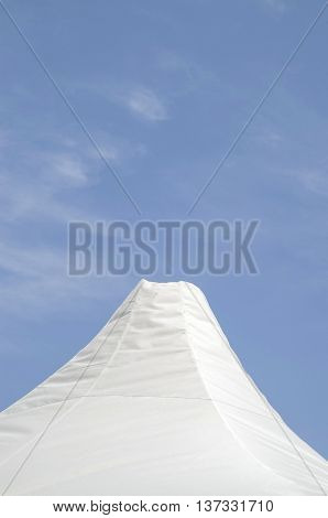 Top of white canvas tent on cloudy sky background