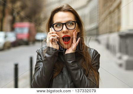 Surprised businesswoman walking down the street while talking on smart phone
