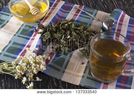 herbal tea, honey and chamomile on wooden background.