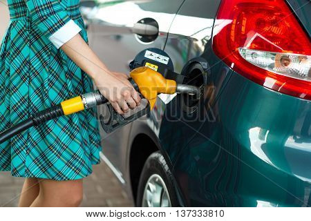 Woman fills petrol into her car at a gas station closeup