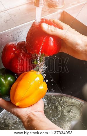 Man's hands wash red paprika. Paprika under flow of water. Ingredient for vegetarian salad. Vegetables that taste good.