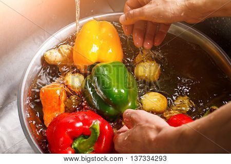 Hands washing paprika and potatoes. Basin with water and vegetables. Best ingredients for soup. Calories and minerals.