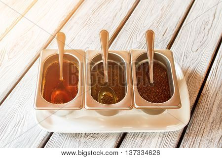 Containers with sauce and spoons. Sauce containers on white plate. Liquid seasonings for meat. Each one tastes different.