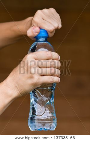 hands opening bottle with fresh water on blurred background
