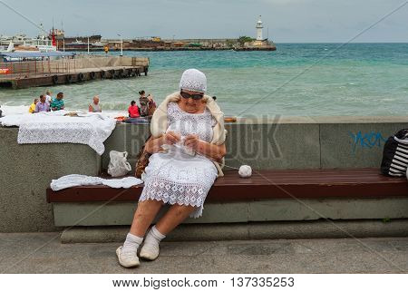 YALTA UKRAINE - MAY 23 2013: Elderly woman doing crochet while sitting on a bench on a Black sea-front in Yalta, Ukraine at May 23, 2013