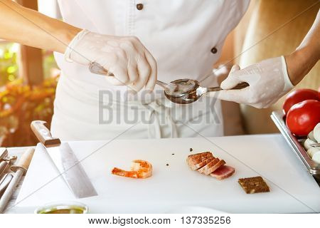 Man's hands holding spoons. Small slices of meat. Work that requires skill. Experienced chef cooking food.