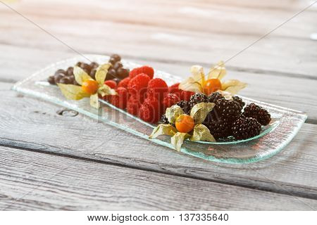 Blackberry and raspberry on plate. Plate with berry dessert. Dessert with flower decoration. Enjoy the summer.