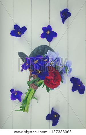 Posy of violets, pansies and ranunculus on white wooden background, retro toned