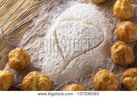 Heart of flour, eclairs and handle mixer on wooden background.