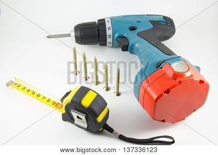 Cordless screwdriver screws and tape measure on a white background