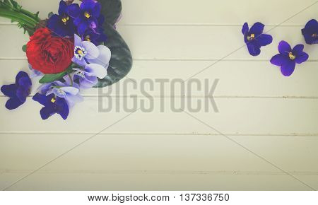 Posy of violets, pansies and ranunculus on white wooden background with copy space, retro toned