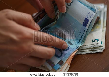 Woman opening brown leather wallet full of euro bank notes