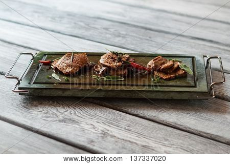 Dark green tray with meat. Cooked meat and small pepper. Freshly cooked veal medallions. Meat dish of european cuisine.