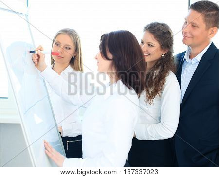 Young business team planning a new strategy standing grouped in front of a flip chart analyzing a chart