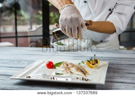 Bottle pours liquid onto fish. Fish with lemon and herbs. Chef adds oil to dish. Delicious dorado fish in restaurant.