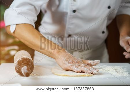 Male hands touching dough. Rolling pin on cooking board. Chef's hand in flour. Precise work of true professional.
