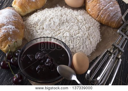 fresh croissant with flour, cherry jam, handle mixer and eggs on wooden background.