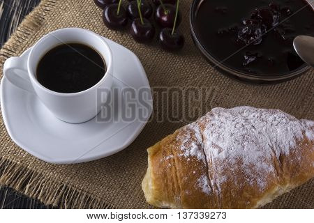 Alarm clock and breakfast with cherry jam, coffee and croissant on wooden background.
