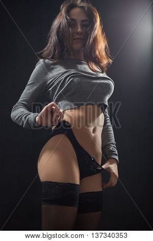 beautiful young woman undressing on black background