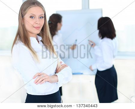 Business woman standing in foreground and her co-workers discussing business matters in the background