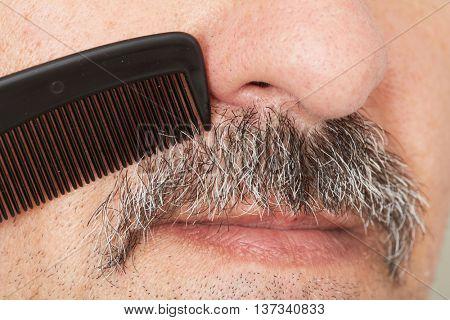 Man combing his mustache.