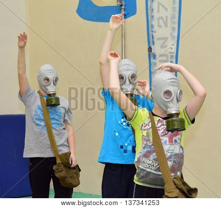 Murmansk, Russia - February 04, 2014, Children wearing gas masks and raised their hands