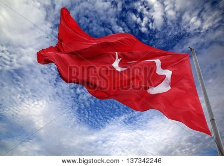 Waving flag of Turkey against blue sky with clouds